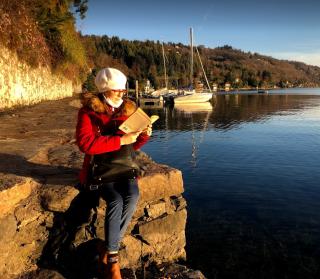 Bilancio libri 2020: ragazza che legge un libro della top 5 libri letti, in inverno sul lago.